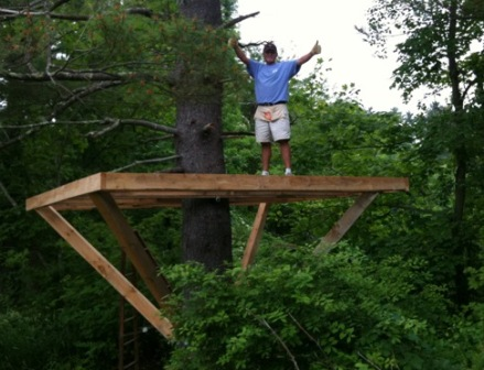 A man stands on a framed treehouse platform in his backyard with several knee braces