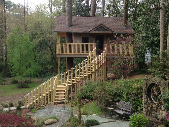 A large adult, 3 tree treehouse with a beautiful and elaberate front stair